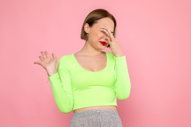 Young woman in green shirt and grey skirt having trouble with stinky smell