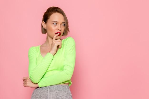 Giovane donna in camicia verde e gonna grigia in posa