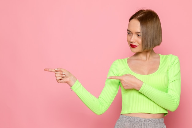 Young woman in green shirt and grey skirt smiling and pointing out with her fingers