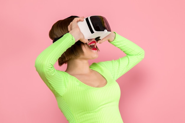 Young woman in green shirt and grey skirt trying out virtual reality playing game