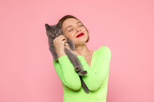 Young woman in green shirt and grey trousers holding cute grey kitten
