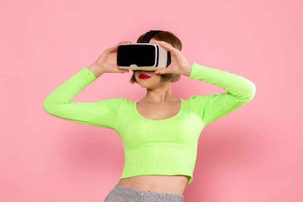 Young woman in green shirt and grey trousers trying out virtual reality game