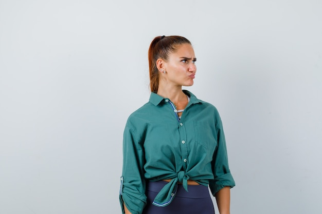 Young woman in green shirt looking away while frowning face, curving lips and looking pensive , front view.