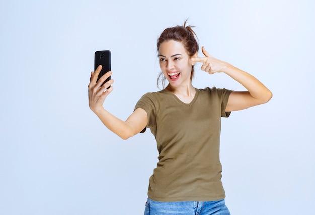 Giovane donna in camicia verde che prende il suo selfie e sembra motivata