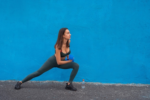 Young woman in green sport cloth holding blue dumbbell isolated on blue. health and  beauty lifestyle