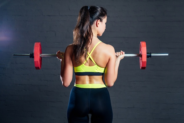Young woman in green sports bra and black pants doing exercises with red barbell on black bricks background.