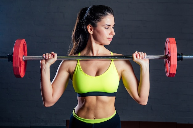 Young woman in green sports bra and black pants doing exercises with red barbell on black bricks background