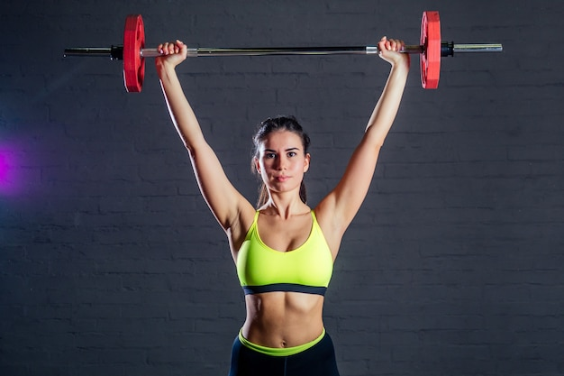 Young woman in green sports bra and black pants trains with red barbell on black bricks background