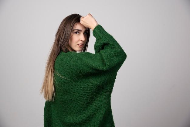 Giovane donna in maglione verde in posa su grigio.