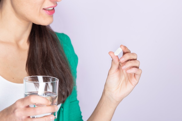 Young woman in green sweater and white shirt holding a pill and a glass of water. medicine and health care concept.