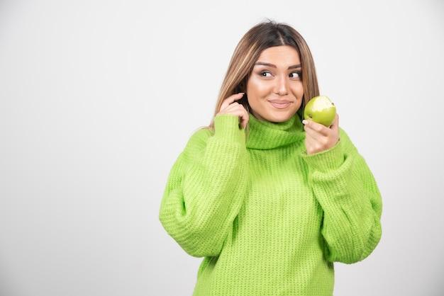 Giovane donna in maglietta verde che tiene una mela.