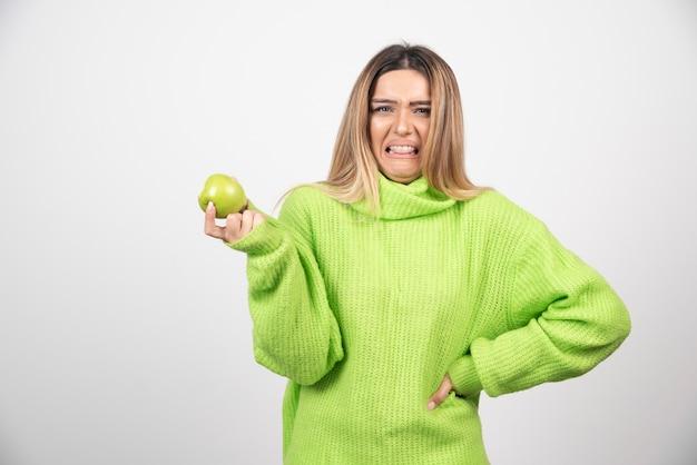 Giovane donna in maglietta verde che tiene una mela