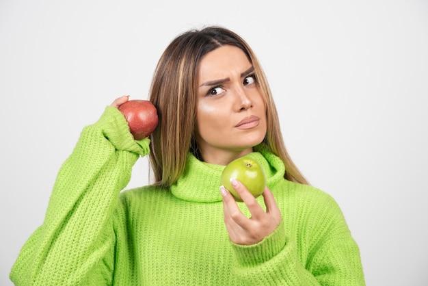 Giovane donna in maglietta verde che tiene due mele in testa.