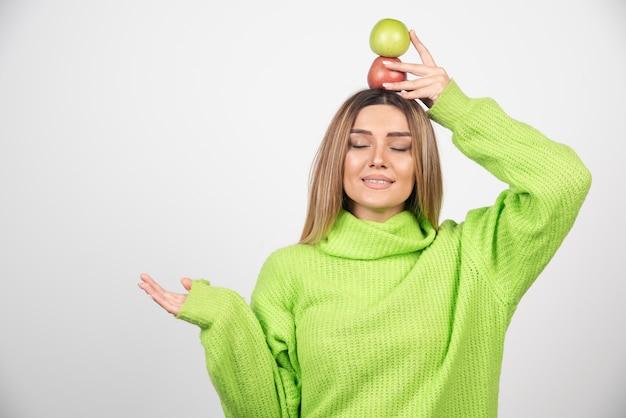 Giovane donna in maglietta verde che tiene due mele in testa