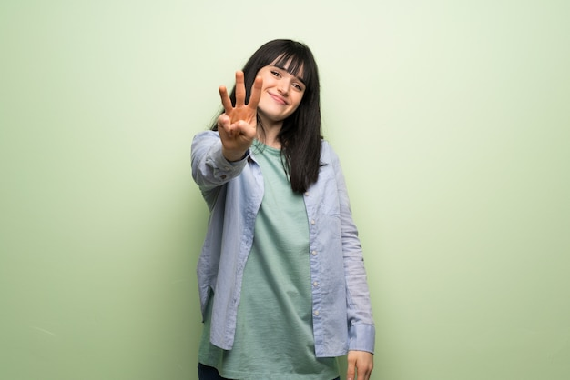 Young woman over green wall happy and counting three with fingers