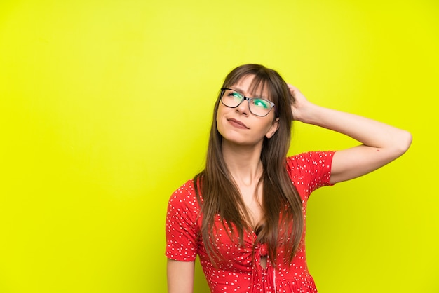 Young woman over green wall having doubts and with confuse face expression
