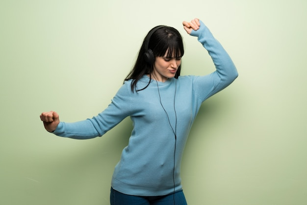 Young woman over green wall listening to music with headphones and dancing