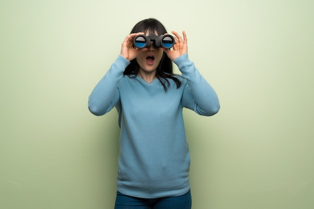 Young woman over green wall and looking in the distance with binoculars