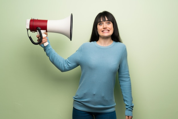Young woman over green wall taking a megaphone that makes a lot of noise