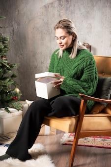 Giovane donna in maglione caldo verde che si siede e che tiene un regalo