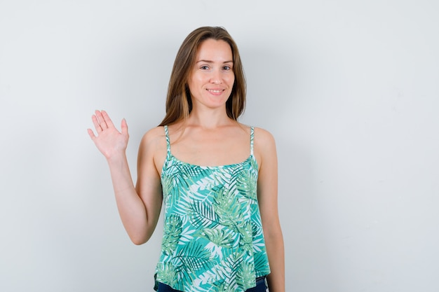 Young woman greeting with open hand and looking cheerful , front view.
