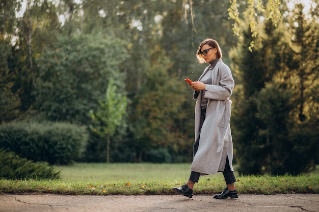 Young woman in grey coat talking on the phone in park