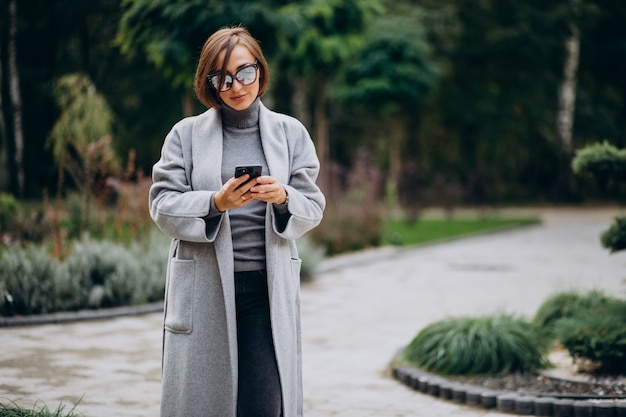 Giovane donna in cappotto grigio che cammina nel parco