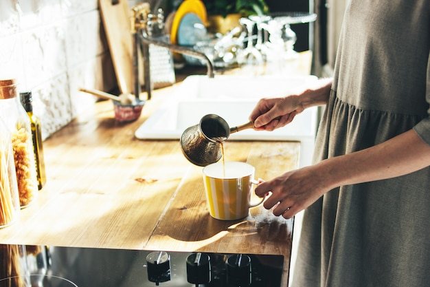 Young woman in grey dress pours natural fresh coffee in a mug in kitchen