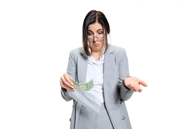 Young woman in grey suit getting a small salary and not believing her eyes. shocked and outraged. concept of office worker's troubles, business, problems and stress.