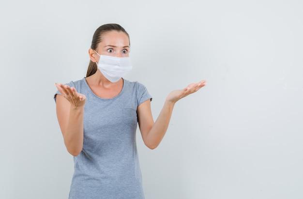 Giovane donna in maglietta grigia, maschera che alza i palmi nel gesto interrogativo, vista frontale.