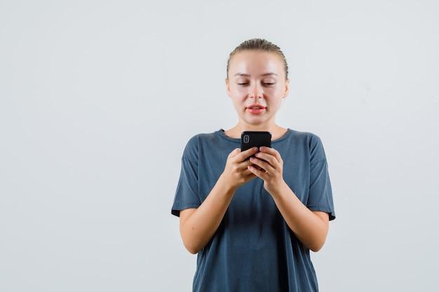 Giovane donna in maglietta grigia che digita sul telefono cellulare e che sembra speranzosa