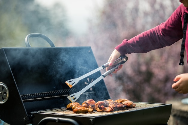 Young woman grills some kind of marinated meat and vegetable on gas grill during summer time