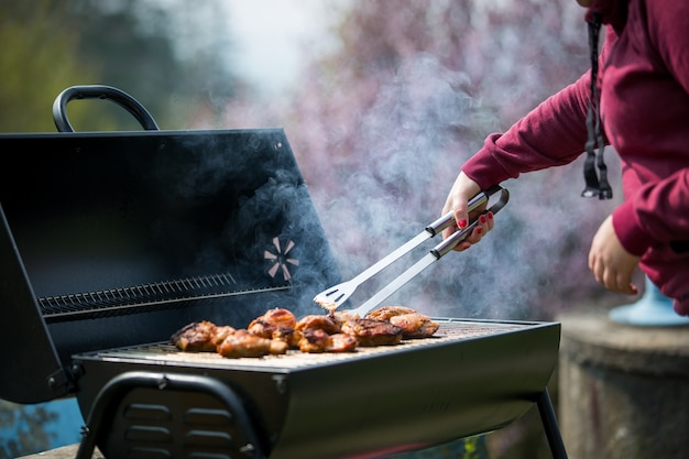젊은 여성이 여름철에 가스 그릴에 절인 고기와 야채를 굽습니다.