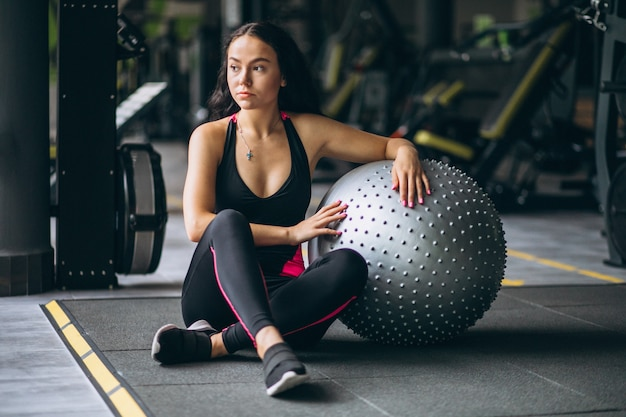 Young woman at the gym exercing with equipment