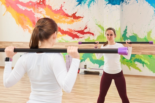 Young woman in the gym performs an exercise with a body bar, looking at herself in the mirror
