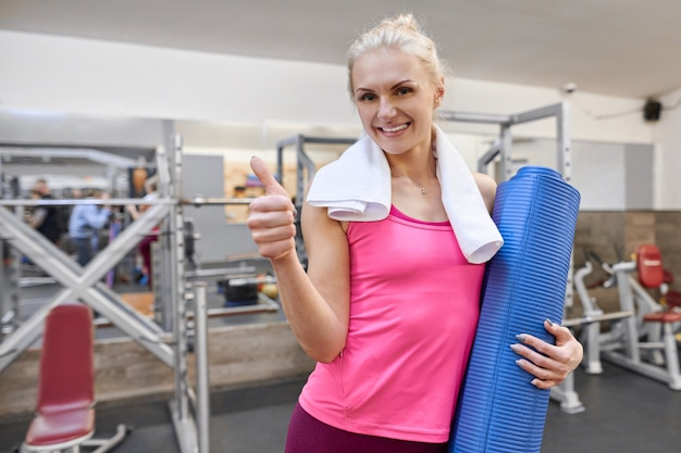 Young woman in gym showing thumbs up