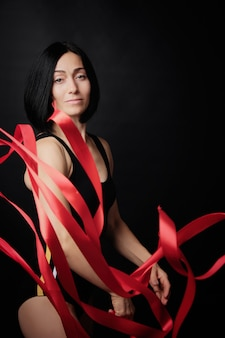 Young woman gymnast of caucasian appearance with black hair spins red satin ribbons
