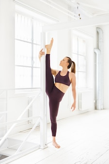 Young woman gymnast doing a vertical split yoga pose using a pole in a high key gym for support to increase suppleness