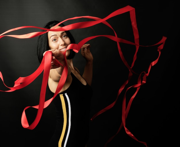 Young woman gymnast spins red satin ribbons