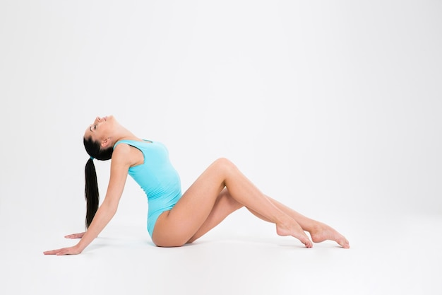 Young woman in gymnast suit sitting on the floor isolated on a white wall