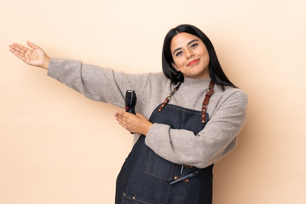 Young woman hairdresser on beige wall extending hands to the side for inviting to come
