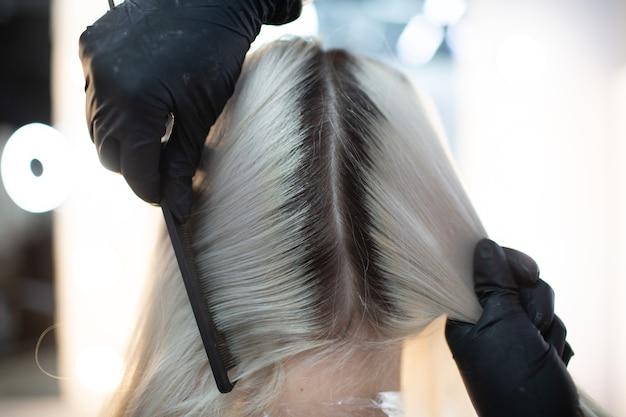 美容院で髪を染めている若い女性の美容師。プロの髪の根の着色