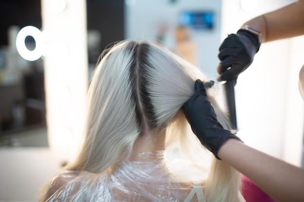 Парикмахер молодой женщины умирая неокрашенные волосы в салоне красоты. профессиональное окрашивание корней волос.