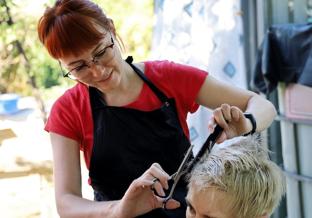Young woman hairdresser smiles while cutting hair to client outdoors