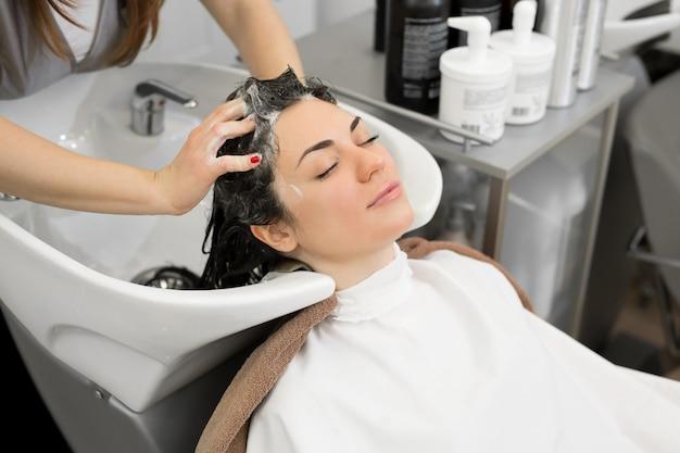 若い女性の美容師はシャンプーで髪を洗い、モダンな理髪店で若い女性の頭をマッサージします