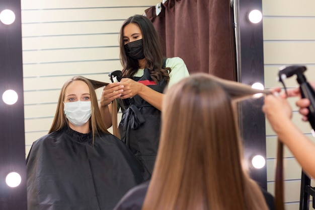 Young woman at hairdresser wearing protective mask