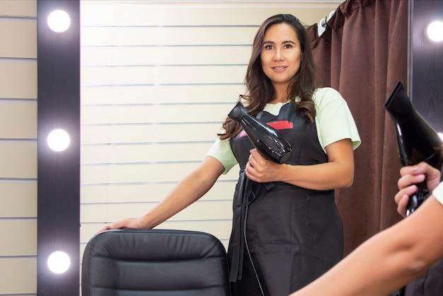 Парикмахер молодая женщина с феном в руках приглашает в салон красоты.