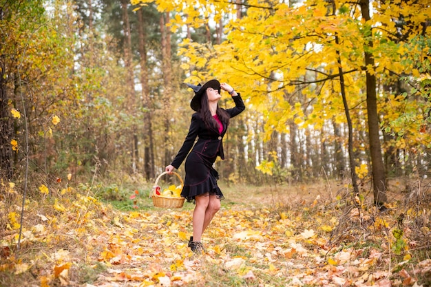 Young woman halloween in a witch costume in a hat in autumn forest autumn days concept