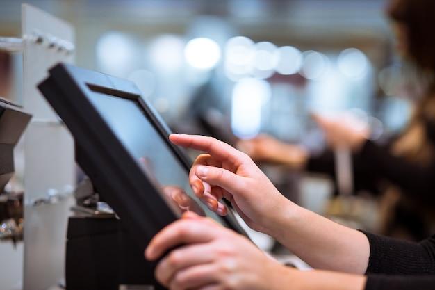 タッチスクリーンのレジ、金融の概念でプロセス支払いを行う若い女性の手
