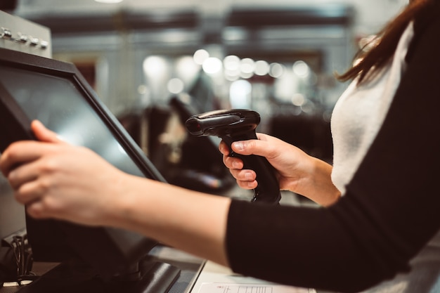 Young woman hand doing process payment on a touchscreen cash register, finance concept